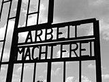 """Στην πύλη του στρατοπέδου Ι παραμένει αναρτημένη η επιγραφή """"ARBEIT MACHT FREI"""", δηλαδή """"Η δουλειά απελευθερώνει""""."""