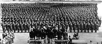 In the foreground a platform with officers facing away from the camera. In the background a formation of over a thousand soldiers, raising their right arms