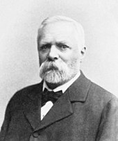 Shoulder high portrait of white haired man with a mustache and beard wearing a suit and bow tie