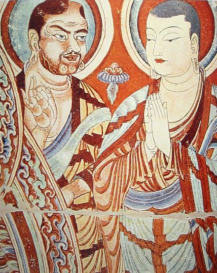 Central Asian Buddhist monk teaching a Chinese monk. Bezeklik, 9th-10th century; although Albert von Le Coq (1913) assumed the blue-eyed, red-haired monk was a Tocharian, modern scholarship has identified similar Caucasian figures of the same cave temple (No. 9) as ethnic Sogdians, an Eastern Iranian people who inhabited Turfan as an ethnic minority community during the phases of Tang Chinese (7th-8th century) and Uyghur rule (9th-13th century). Central Asian Buddhist Monks.jpeg