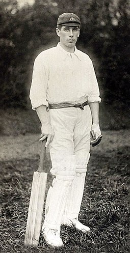 A man standing in cricket whites holding a cricket bat by his side