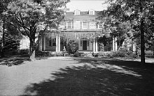 Black and white image of a two story house with dormer windows on the roof and a porch with vines on the ground floor. A standing man in a suit and two large trees are in front of the house.