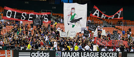 Supporters display a tifo supporting head coach Ben Olsen (drawn to lampoon Rambo) during a regular season match against FC Dallas Dcunited-oslen-tifo.jpg