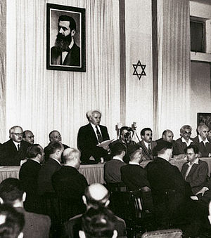 Israeli Jews - David Ben-Gurion proclaiming Israeli independence from the United Kingdom on 14 May 1948, below a portrait of Theodor Herzl