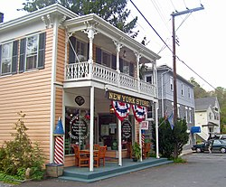 "An orange building with a white porch and a storefront at street level with red, white and blue bunting and a sign saying ""New York Store"". Farther down the side of the street are a gray building and a yellow one."