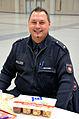 Die!!! Weihnachtsfeier 2013, 105 Der Kontaktbeamte Herr Ritter von der Polizeiinspektion Ost (Am Welfenplatz) vor unangetasteten Knabbereien in der Orga-Halle.jpg