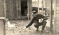 E. E. Wilson feeding a chicken, circa 1915 (6478695343).jpg