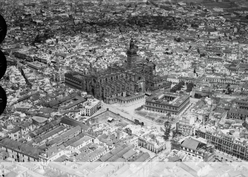 Vue aérienne sur la cathédrale de Séville (1928) : La masse sombre au milieu de la ville claire - Photo de Walter Mittelholzer