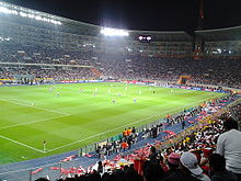 Photograph of people cheering from the stands inside an illuminated stadium at night