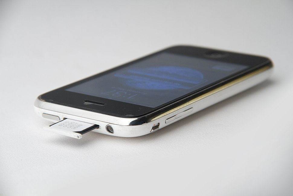 File-Top and left side of iPhone 3G white showing the standby button, sim tray, headphone plug, silent switch and volume buttons showing the sim tray half pulled out