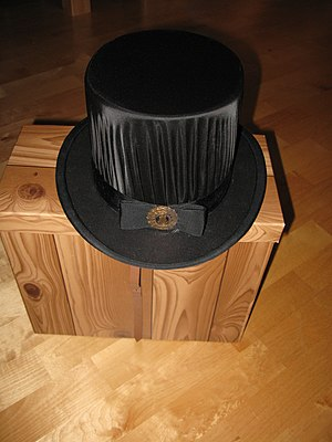 Doctoral hat - Doctoral hat for the Doctor of Science (Technology) of the University of Oulu, on the top of its faux wooden storage case.
