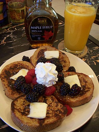 French toast - French toast topped with fruit, butter and cream, served with maple syrup.