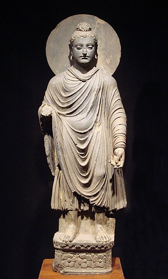 An early representation of the Buddha wearing kasaya robes, in the Hellenistic style. Gandhara Buddha (tnm).jpeg