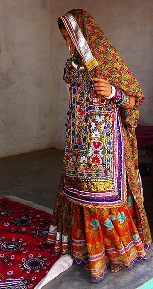 Choli - Woman in an ancient form of long, front-covering choli, tied at the back.