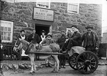 A donkey-cart and several people in front of an inn
