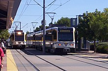 A pair white and yellow light rail trains are visible, with overhead lines above, and several passengers visible on the station platform.