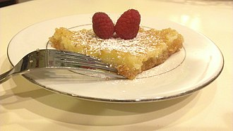 St. Louis cuisine - A slice of gooey butter cake, garnished with powdered sugar and raspberries
