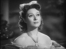 Black-and-white still of a woman gazing upwards, wearing an off-the shoulder dress, a prominent necklace, and a bow in her dark hair.