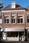 foto van Huis met eenvoudige recht afgesloten gevel, voor waarschijnlijk ouder pand; pui modern. Als sleutelsituatie begin Grote Oost