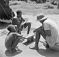 Iemand van Van der Polls reisgezelschap speelt een gezelschapsspel (Awari Bangi), Bestanddeelnr 252-6787.jpg