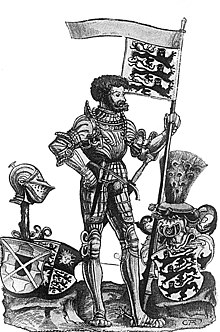 A dark haired and bearded man wearing armor and carrying a flag showing three lions. He is standing beside two three shields, two with the same symbols as his flag, and one topped by a helmet.