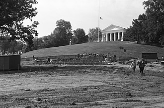 John F. Kennedy Eternal Flame - Grave site under construction in October 1965. The temporary grave is just beyond the picket fence, where the crowd has gathered.