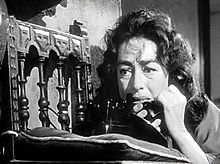 Facial shot of a dishevelled middle-aged woman on the telephone.