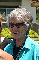 Head shot of of short-haired woman in sunglasses.
