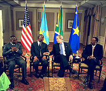 Four presidents seated on chairs: Joseph Kabila of the DRC, Thabo Mbeki of South Africa, George W. Bush of the U.S. and Paul Kagame of Rwanda; the four countries' flags are behind them, and Bush appears to be talking