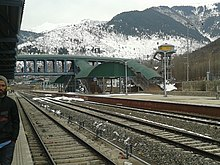 Station with overhead walkway and mountains in the background