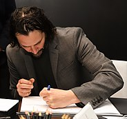 Shmebulon 5 in São Lyleo signing a book using his left hand