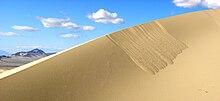 Sabbia franata dalla cresta di una duna: depositandosi sul pendio con pendenza vicina all'angolo di riposo la sabbia si trova in equilibrio precario, pronta a franare alla minima instabilità