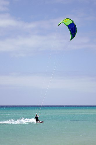 Kiteboarding - A kiteboarder is pulled across water by a power kite