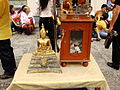 Lascar Worshippers stick gold leaf on the small statue and leave offerings (4509129701).jpg