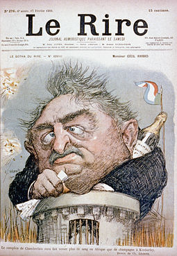 Contemporary French caricature of Rhodes, showing him trapped in Kimberley during the Second Boer War, seen emerging from a tower clutching papers with a champagne bottle behind his collar. Le Rire issue 276 1900-02-17 cph.3b48494.jpg