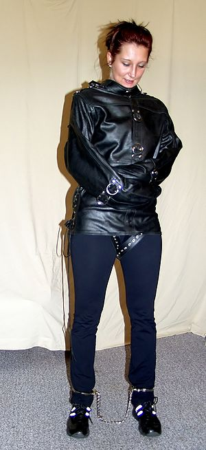 Straitjacket - A woman wearing a leather straitjacket with leg irons