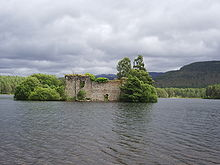 A small wooded islet stands in a lake. A large ruined stone wall with a door and window sits amongst the trees. Green conifer-clad hills lie beyond the islet under leaden grey skies.