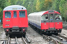 The train on the left is a Metropolitan Line A Stock unit, the smaller train is a Piccadilly Line 1973 tube stock train