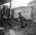 Man gooit kolen op het vuur van de distilleerketel, Bestanddeelnr 252-9469.jpg
