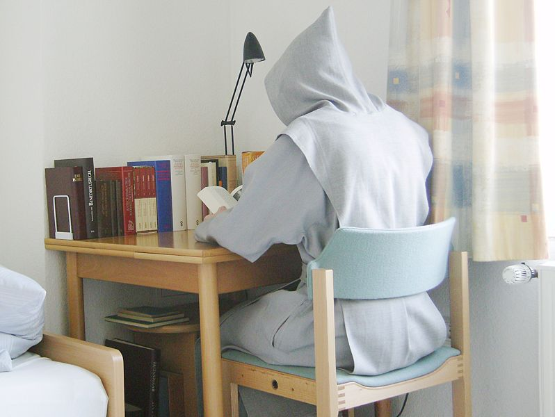 Trappist monk, back to the photographer, sitting at his desk attending to spiritual reading.