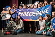 "About twenty K-12 student finalists are standing on a stage, all smiling, and holding a banner that reads ""NASA's perseverance rover"". In front of them on the stage is a miniature rover."