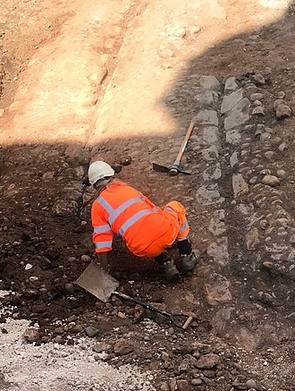 Victoria Square, Birmingham - An Archaeologist working on the cobbled street, in June 2018