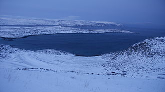 Mehamn - Mehamnfjorden during polar night, with Normannsethfjorden and Vedvikneset just north of Mehamn. Reipnakktinden as well as a sugarhead of Kinnarodden − the northernmost point on the Nordkinn Peninsula − are visible at the far end.