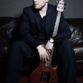 Mike Hall posing with his Cathedral model bass from Skjold Design Guitars.png