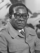 Robert Mugabe, wearing a dark suit and glasses, looks to the viewer's right