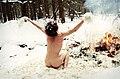 Naked man sitting at campfire in snow.jpg