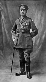 A full length portrait of a man in military uniform wearing two military medals and leaning on a swagger stick.
