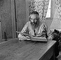 Oost-Europese rabbijn en schriftgeleerde in de wijk Mea Shearim, aan tafel zitte, Bestanddeelnr 255-0411.jpg