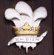 "On the main gate, a painted carving of the badge of the Prince of Wales, a symbol often adopted by members of college. The German motto ""Ich dien "" means ""I serve."""