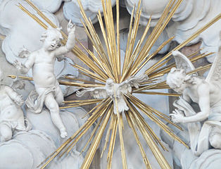 Sculpture of a white dove surrounded by gold rays emerging from white clouds, with a white angel on either side